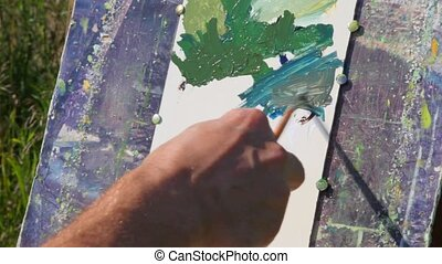 hand of man painting landscape by brush and oil paint