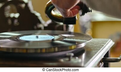 Hand of man putting vintage gramophone in starting position,...