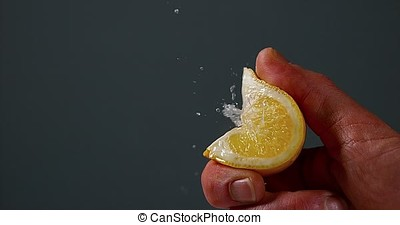 Hand of Man Squeezing Lemon, citrus limonum against Black...