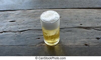 Hand of man taking beer with ice in glass