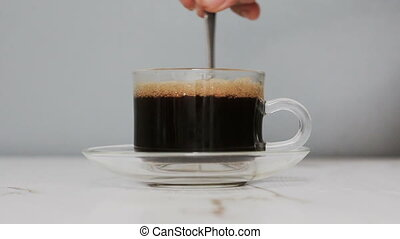 Hand of man using coffee spoon to mix black and hot coffee into a clear cup of coffee Close up shot
