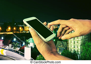 hand of man using mobile phone on view of city in night time background