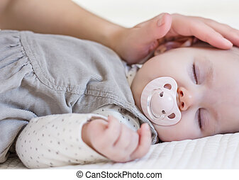 Hand of mother caressing her baby girl sleeping