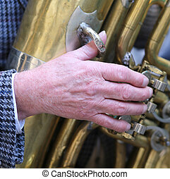 hand of old man plays the trombone brass