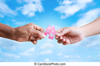 Hand of old women giving paper card house to young woman...