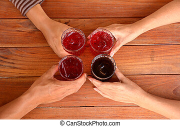 hand of people holding a glass of sweet drink with ice cubes on wooden table background.
