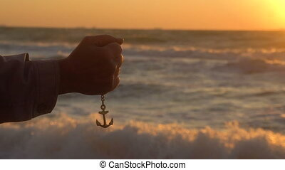 Hand of Sailor Man Drops the Anchor on Chain with Beautiful sunset above the Black sea at Background