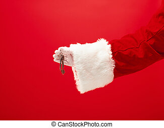 Hand of Santa Claus holding a gift on red background