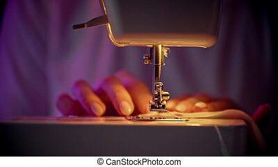 Hand of seamstress puts a thread in the eye of a needle