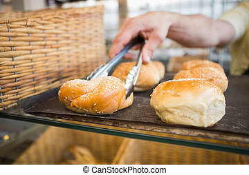 Hand of server taking bread with tongs