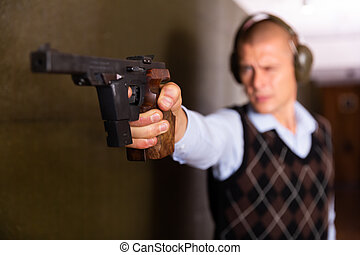 Focused shooter practicing sport handgun shooting at firing range. Selective focus on male hand squeezing pistol grip and pressing trigger.