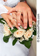 Hand of the bride and hand of the groom with rings over a wedding bouquet against a white dress