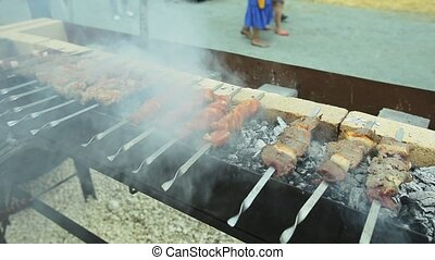 Hand of the cook with skewers with meat which are fried over...