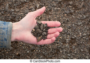 Hand of the farmer holding handful of infertile earth - Hand...