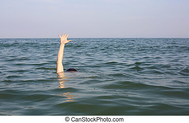 Hand of the person seeking help while drowning in the ocean