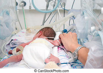 the physician and newborn in incubator - Hand of the ...
