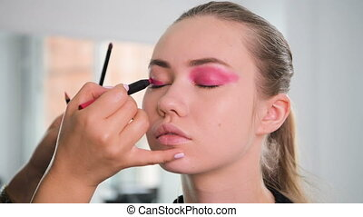 Hand of visagist, eyeshadow brush. Young woman, colorful...