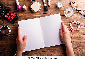 Hand of woman holding empty greeting card. Make-up products.