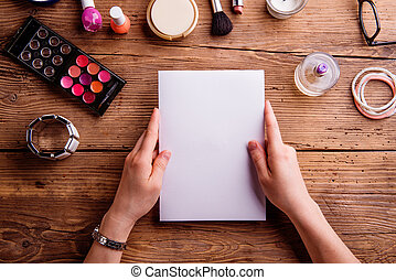 Hand of woman holding greeting card. Make up products.