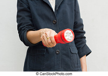 Hand of woman holding red flashlight