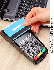 Hand of woman paying with contactless credit card with NFC technology, finance concept