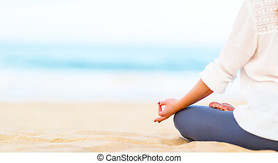 hand of woman practices yoga and meditates on beach