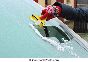 Hand of woman scraping ice from car windscreen