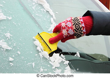 Hand of woman scraping ice from car windscreen - Hand of...