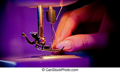 Hand of woman seamstress puts a thread in the eye of a needle