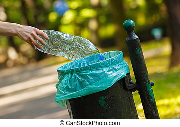 Hand of woman throwing plastic bottle into recycling bin, littering of environmental