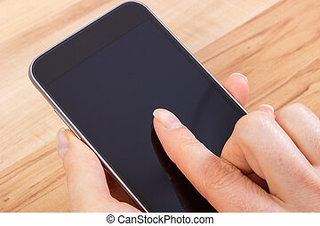 Hand of woman touching blank screen of mobile phone