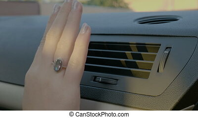 Hand of woman turning ac heat on in car