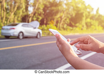 Hand of woman using smartphone and blur of her broken car parking on the road. Contacting car technician or need help concept