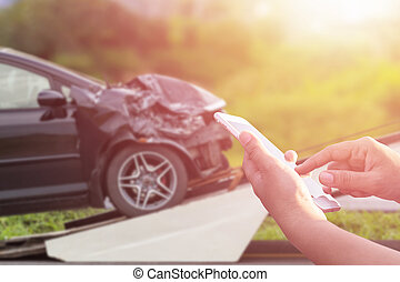 Hand of woman using smartphone and blur of her broken car parking on the road. Contacting car technician, Insurance or need help concept