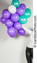 Hand of woman with colored balloons