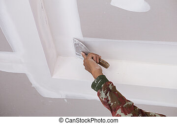 hand of worker using gypsum plaster ceiling joints at...