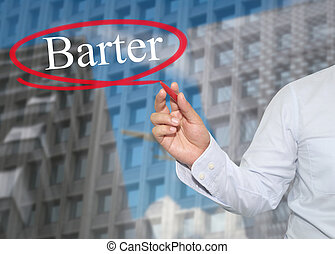 Hand of young businessman write the word Barter on ...