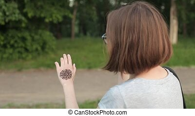 Hand of young caucasian woman in eyeglasses with floral...