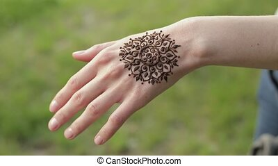 Hand of young caucasian woman with floral mehndi tattoo....