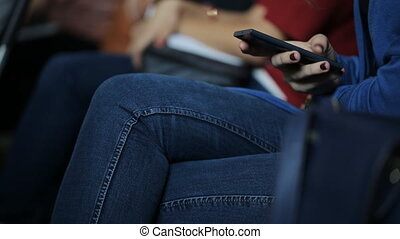 Hand of young female in jeans with painted nails uses smartphone