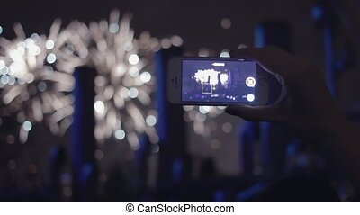 Hand of young girl with smartphone. Woman shoots fireworks...