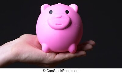 Hand of young man holding piggy bank against black...