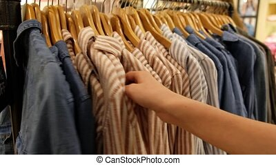 Hand of young woman choosing shirt in department store - ...