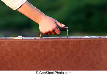 hand of young woman with a suitcase