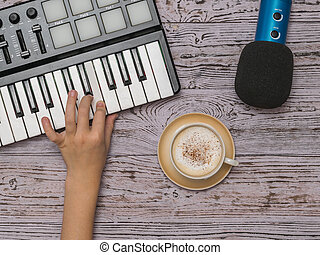 Hand on a music mixer, a microphone and a Cup of coffee on a wooden table. The process of creating music. The view from the top.