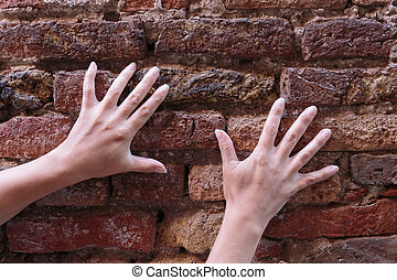 hand on an old brick wall