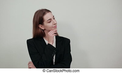 Hand on chin thinking about question, pensive expression. Doubt. Thoughtful face. Using that incredibly sharp business mind. Young attractive woman with brown hair in a light t-shirt and black jacket