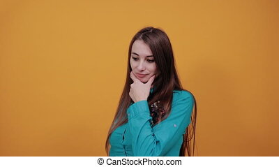 Hand on chin thinking about question, pensive expression. Doubt. Thoughtful face. Using that incredibly sharp business mind. Young attractive woman with brown hair and eyes, blue shirt, yellow