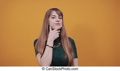 Hand on chin thinking about question, pensive expression. Doubt. Thoughtful face. Using that incredibly sharp business mind. Young attractive woman, dressed green shirt blonde hair, yellow background