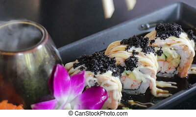 Hand On Chopsticks Having Salmon Sushi With Black Ebiko